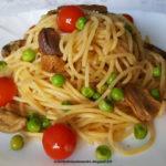 Spaghetti con porcini secchi, pomodorini e piselli